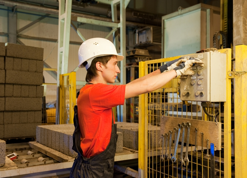 A worker interacts with a control panel mounted on a piece of wire mesh.
