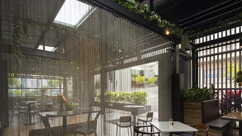 A mesh curtain divides two parts of a restaurant.
